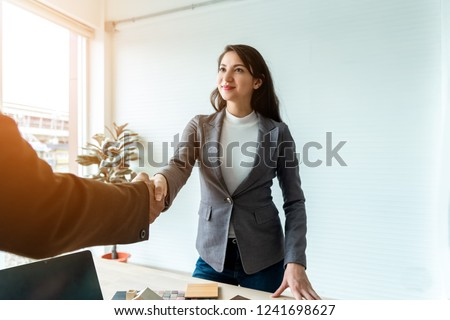 Meeting of Insurance agent and customer shaking hands after signing a contract for realty purchase in the office .Bank employee congratulate.Home loan approval ,insurance mortgage, real estate concept #1241698627