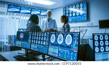 Meeting of the Team of Medical Scientists in the Brain Research Laboratory. Neurologists / Neuroscientists Having Analytical Discussion Surrounded by Monitors Showing CT, MRI Scans.