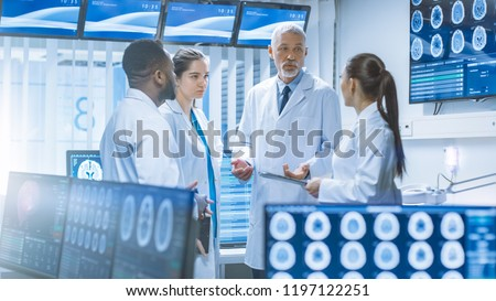 Meeting of the Team of Medical Scientists in the Brain Research Laboratory. Neurologists / Neuroscientists Having Heated Discussion Surrounded by Monitors Showing CT, MRI Scans.