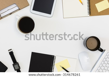 meeting office desk from top view , black and white coffee mug,black watch,mouse,keyboard,black and brown notepad, yellow post it note,folder,tablet ,yellow pencil with white background / meeting room