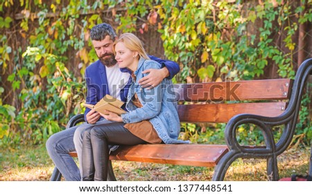 Meeting people with similar interests. Man and woman sit bench park. Read same book together. Couple interested literature. Literature common interest. How to find girlfriend with common interest.