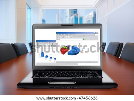 meeting room, in front focus placed on graph shiwing progress on laptop screen - stock photo