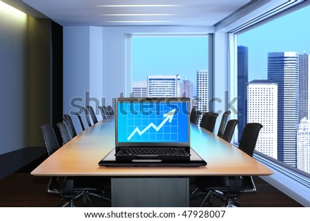 meeting room, in front focus placed on graph shiwing progress on laptop screen
