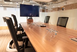 meeting room with clear acrylic sheet separates the center on the conference table to prevent COVID-19 and face shield on the table.