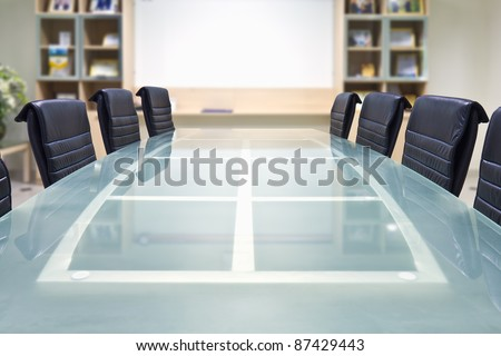 Meeting room with glass top table and armchairs, office interior