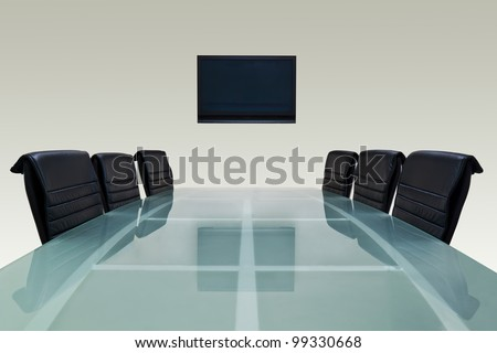Meeting room with glass top table , armchairs and television. Office interior