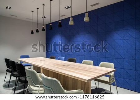 Meeting room with luminous lamps in an office with gray and textured blue walls. There are wide wooden tables with multicolor chairs, hanging dark and light lamps. Horizontal.