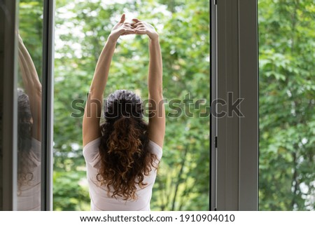 Meeting summer day. Back rear view of happy young woman stand in balcony door stretch hands enjoy weekend have pleasure. Calm beautiful female do morning exercises practice yoga by opened large window