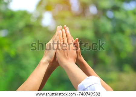 Meeting teamwork concept,Friendship,Group people with stack of hands showing unity on natural green background #740749582