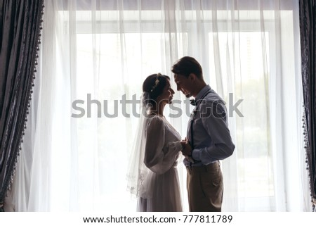 Meeting the bride and groom in the bedroom, the newlyweds are happy. Man with flowers in his hand. Love. Embrace. silhouette opposite the window