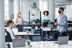 Meeting with manager and protecting health after returning to office after quarantine. Boss in protective mask with tablet speaks to multiracial of workers in office interior with devices, empty space