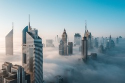Mega tall skyscrapers of Dubai covered in early morning think fog. Rare aerial perspective.