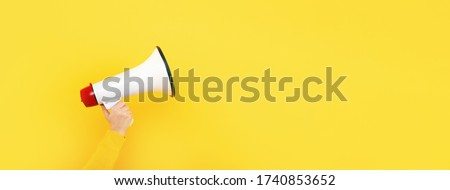 megaphone in hand on a yellow background, attention concept announcement, panoramic mock-up Stockfoto ©