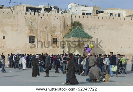 MEKNES - APRIL 18: Moroccan people walking on the square near the city wall in Meknes April 18, 2010 in Fes, Morocco. - stock photo