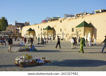 MEKNES, MOROCCO - NOVEMBER 19: Unidentified people, street vendors and street performers on place el-Hedim with medieval wall, on November 19, 2014 in Meknes, Morocco