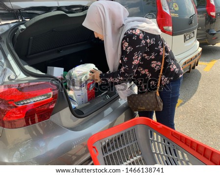 MELAKA, MALAYSIA. July 29 , 2019: Asian girl shopping with mid year sales promotion in department store and go to car park for keep her bag in the car #1466138741