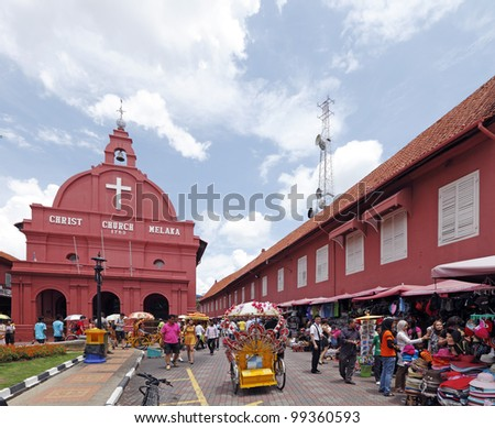 MELAKA, MALAYSIA - MARCH 11: Colorful trishaw with tourist at the historical Christ Church on March 11, 2012, in Melaka City, Malaysia. Melaka city is a designated UNESCO world heritage site. - stock photo