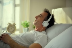 Melancholic adult man with lost eyes listening to music with white headphones from the mobile lying on the bed entering sunset light