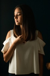 Melancholic girl with her hand on her chest wearing white blouse on dark blue background