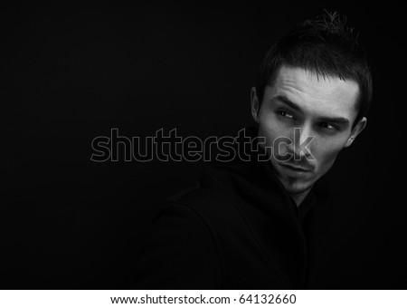 Melancholic guy on dark background.