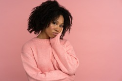 Melancholic sad African woman looking at camera with thoughtful expression. Depressed Afro-American girl keep hand on cheek, has skeptical expression, wear pink sweater isolated on pink studio wall.
