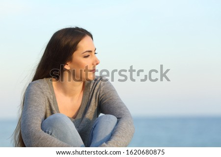 Melancholic woman complaining looking away sitting on the beach
