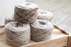 Melange yarn skeins on a wooden box in a light room. Beige-brown colored yarn. Bobbins of yarn.