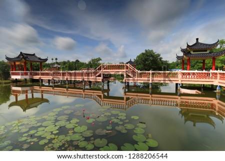 Melati Lake with chinese architechtural bridge along the lake. The lake located in Perlis, Malaysia. Beautiful reflection of chinese architectural bridge on the lake.