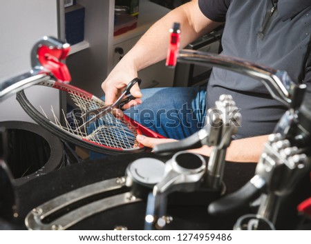 Melbourne, Australia, 2009, January 17: Racquet stringer weaving cross strings of synthetic gut string in a Tennis racquet on a electronic tournament stringing machine.
