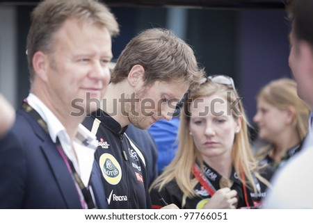 MELBOURNE, AUSTRALIA - MARCH 16: Lotus Renault driver Romain Grosjean sings autographs on the first day of the Australian Formula 1 Grand Prix on March 16, 2012 in Melbourne, Australia