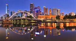 Melbourne CBD cityline at sunrise reflecting bright city illumination lights in still yarra river waters