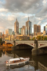 Melbourne City Skyline Cityscape and White Tour Boat Ferry cruise under Princes Bridge with Dramatic Golden Sky at Sunset in Summer Daytime, Australia