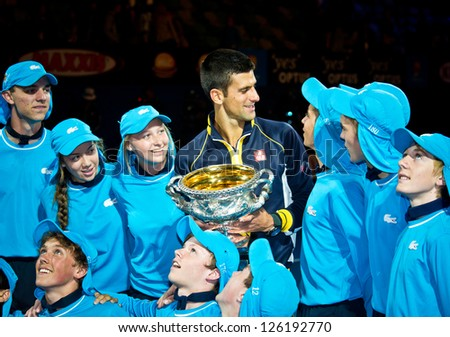 MELBOURNE JANUARY 27 Novak Djolovic of Serbia with ballkids and the trophy for winning the 2013 Australian Open on January27 2013 in Melbourne Australia