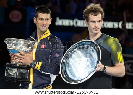 MELBOURNE - JANUARY 27: Runner-up Andy Murray of Scotland (R) is watched by winner Novak Djokocvic   at the trophy presentation at the 2013 Australian Open  on January27, 2013 in Melbourne, Australia.