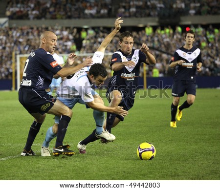 MELBOURNE - MARCH 20: Melbourne Victory captain Kevin Muscat (L) lays a heavy tackle on a Sydney FC opponent  in the  A-League grand on March 20, 2010 in  Melbourne.