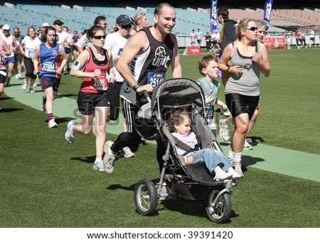 MELBOURNE - OCTOBER 11: A man and child in a pusher compete in the 2009 Melbourne marathon. October 11, 2009 in Melbourne.