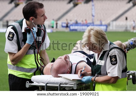 MELBOURNE - OCTOBER 12: An exhausted competitor receives medical attention after completion of the Melbourne marathon October 12, 2008.