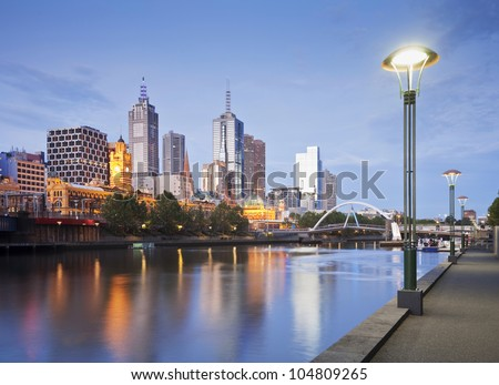 Melbourne skyline early on a summer evening, just as the lights start to come on, reflecting in the Yarra River. - stock photo