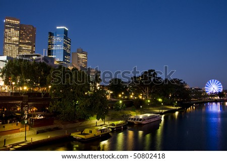 Melbourne skyline on yarra river at night with reflection in the water and the colorful ferris wheel.