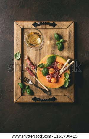 Melon and ham salad served in half of Cantaloupe melon with fresh basil and grissini bread on wooden serving tray over dark brown texture background with glass of white wine. Flat lay, space #1161900415