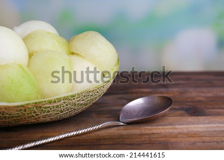 Melon in melon peel on wooden table on natural background