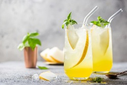 Melon juice, lemonade in glasses with ice and melon slices garnished with basil leaves. Concept of fresh summer drink