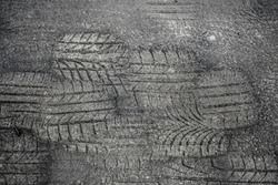 Melt asphalt imprint. Tyre mark texture. Tire track on the road background. Highway street damaged with sunlight heat. Tire imprints on old  asphalt road in black and white