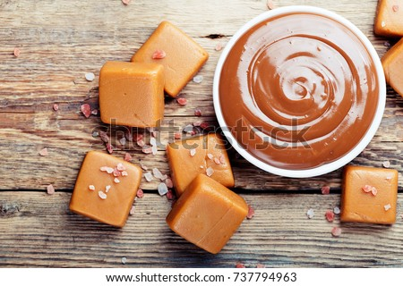 Melted caramel with pieces of caramel candy with salt on a wooden table.