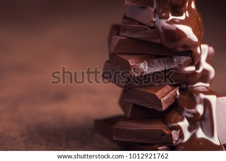 melted chocolate pouring into a piece of chocolate bars with green mint leaf on a table