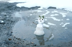 melted cute snowman in puddle. bad warm rainy winter weather.  anomaly weather concept. copy space