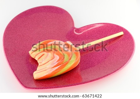 Melted lollipop on brightly colored heart shaped plate