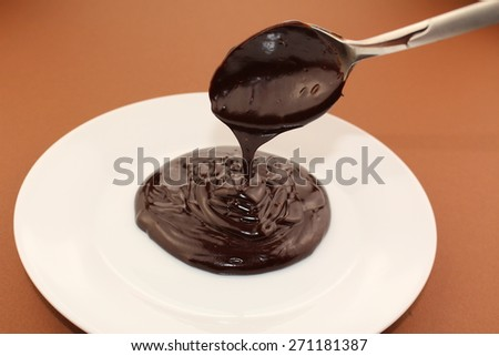 Melted semi-liquid bitter chocolate flowing onto a white plate