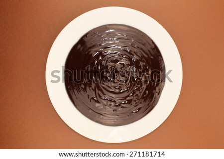 Melted semi-liquid bitter chocolate on a white plate