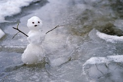 melted snowman in puddle. bad warm rainy winter weather.  anomaly weather concept. autumn, winter, spring seasons.